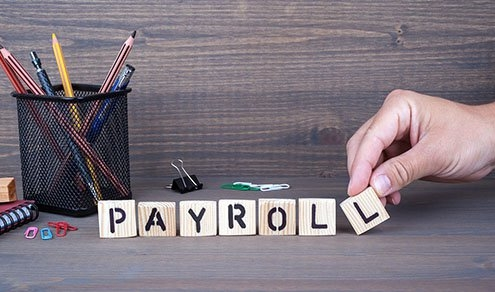 payroll. Wooden letters on dark background
